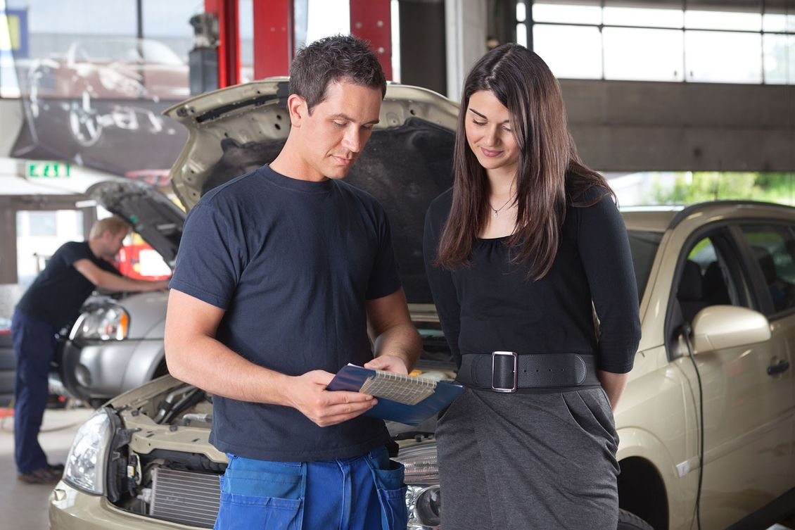 Mechanic reading a report to a customer